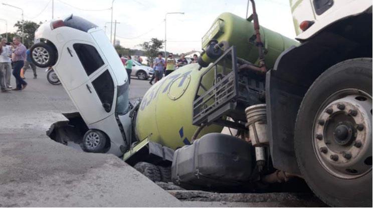 """El auto y el camión fueron """"tragados"""" por el pozo."""